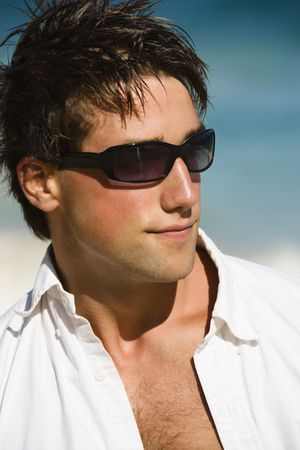 Head and shoulder portrait of attractive man wearing sunglasses on Maui, Hawaii beach.
