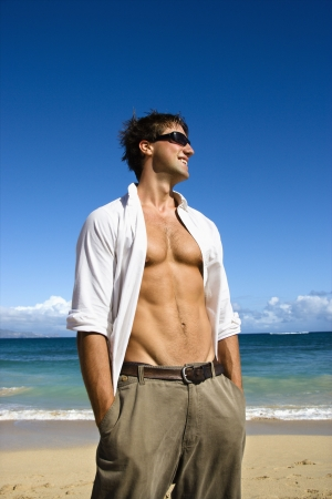 Portrait of attractive man standing with shirt unbuttoned wearing sunglasses on Maui, Hawaii beach. photo