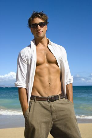 Portrait of attractive man standing with shirt unbuttoned wearing sunglasses on Maui, Hawaii beach. Stock Photo