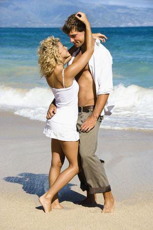 Attractive couple in sensual embrace on Maui, Hawaii beach. Stock Photo