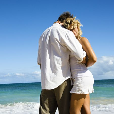 Attractive couple in embrace on Maui, Hawaii beach. photo