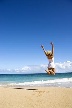 Pretty young woman jumping on Maui, Hawaii beach with arms raised into air.