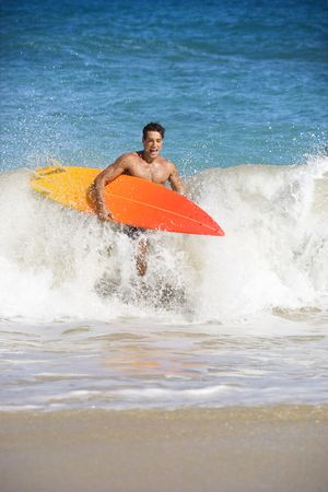 Attractive young man running out of water carrying surfboard in Maui, Hawaii. Stock Photo - 2115318