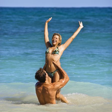 Man holding woman up out of water on Maui, Hawaii beach. photo