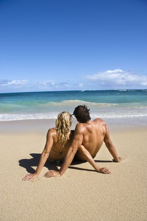 Couple sitting close together on Maui, Hawaii beach looking out at ocean. Stock Photo - 2095827