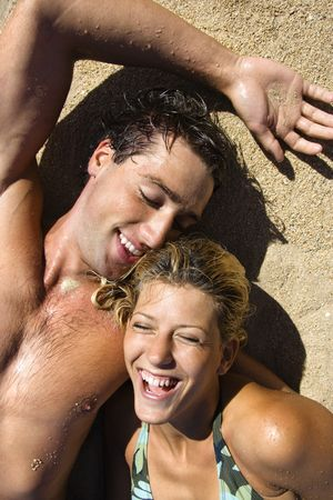 Smiling happy couple lying in sand on Maui, Hawaii beach. Stock Photo - 2115425