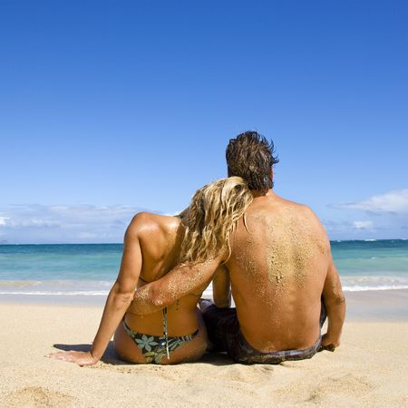 Rear view of couple sitting on Maui, Hawaii beach with woman leaning head on man's shoulder. Stock Photo - 2095826