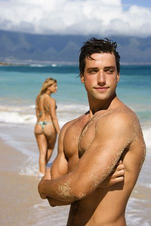 bare body women: Handsome man standing on Maui, Hawaii beach with woman in background.