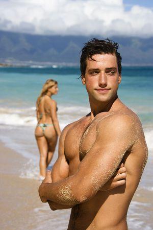 nackte brust: Handsome Mann steht auf Maui, Hawaii Strand mit Frau im Hintergrund.
