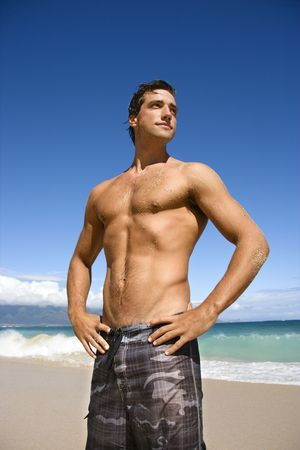 beach hunk: Handsome man standing on Maui, Hawaii beach.