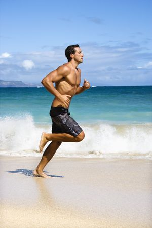 excercise: Physically fit man running on Maui, Hawaii beach.