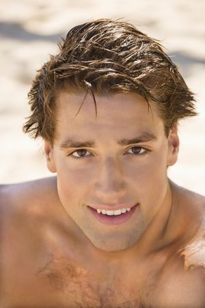 beach hunk: Head and shoulder portrait of handsome man on beach. Stock Photo