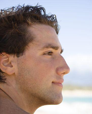 hombres sin camisa: La cabeza y el hombro perfilan el retrato del hombre hermoso en la playa.