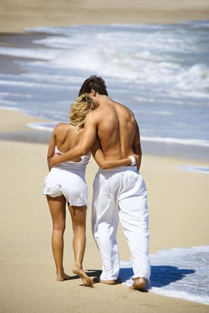 eachother: Attractive couple walking on Maui, Hawaii beach with arms around eachother.