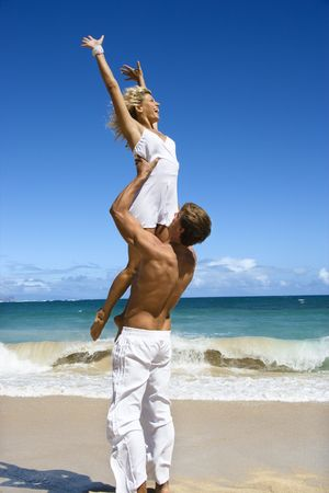 Man holding woman up in air on Maui, Hawaii beach. photo