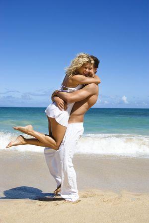 Couple in emotional embrace on Maui, Hawaii beach.
