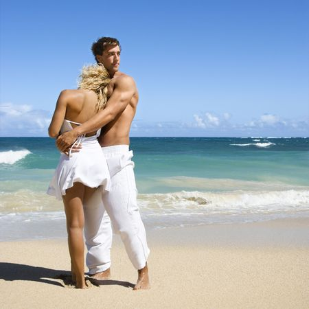 Attractive couple standing on Maui, Hawaii beach holding eachother. photo