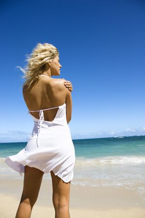 Portrait of pretty blond woman standing on Maui, Hawaii beach looking out towards ocean. photo
