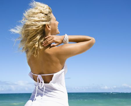 Portrait of pretty blond woman smiling standing on Maui, Hawaii beach looking out towards ocean. photo