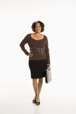 attache: Full length portrait of businesswoman standing with hand on hip holding briefcase. Stock Photo