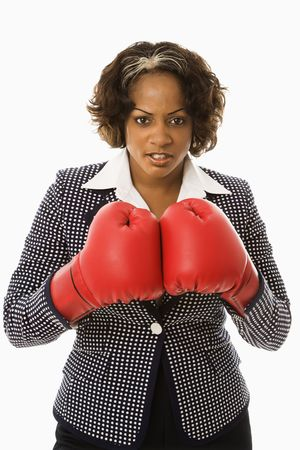 Businesswoman wearing boxing gloves looking serious. photo
