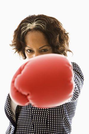 Businesswoman wearing boxing gloves punching. photo