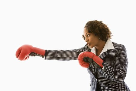 woman boxing gloves: Businesswoman wearing boxing gloves punching. Stock Photo