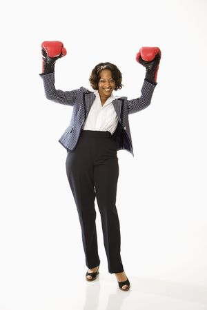 triumphant: Businesswoman wearing boxing gloves holding arms up in victory stance and smiling.