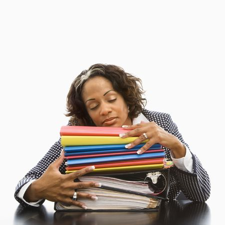 Businesswoman resting head on large stack of books and files with eyes closed.