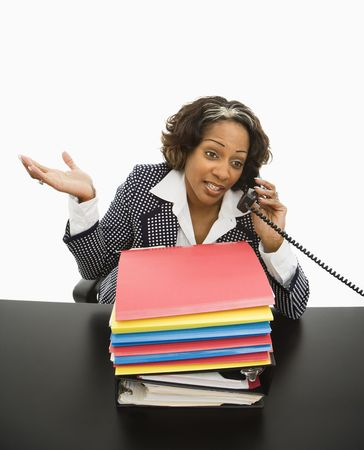 Businesswoman sitting at office desk with large stack of work talking on telephone and gesturing. photo