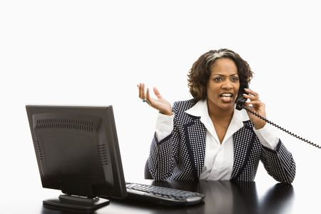 Businesswoman sitting at office desk with computer talking on telephone looking upset. photo