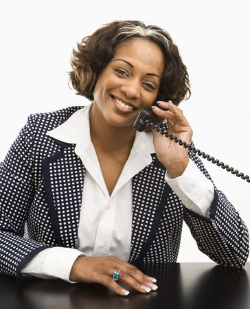 Businesswoman sitting at desk holding telephone receiver to ear smiling. photo