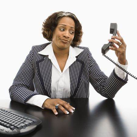 Businesswoman sitting at desk holding telephone receiver out away from head looking with strange expression. photo