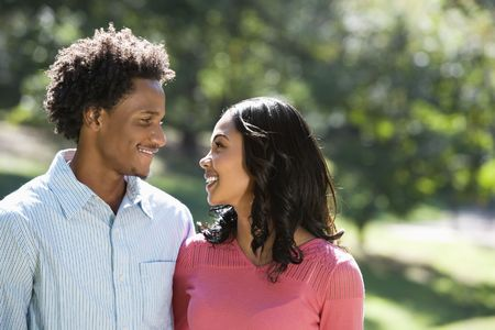 Attractive couple in park looking at eachother smiling. Stock Photo - 2115335