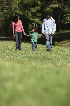 Parents and young son walking in park holding hands. Stock Photo - 2115269