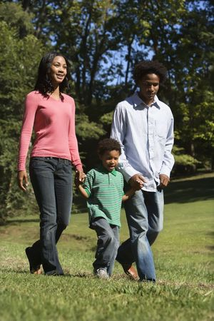 Parents and young son walking in park holding hands. photo
