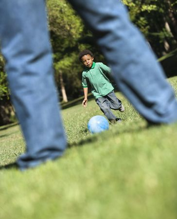 Son running and kicking ball towards father in park. Stock Photo - 2115308