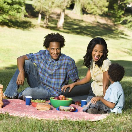 Smiling happy parents and son having picnic in park. Stock Photo
