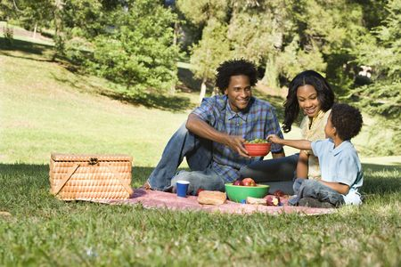 family health: Smiling happy parents and son having picnic in park. Stock Photo