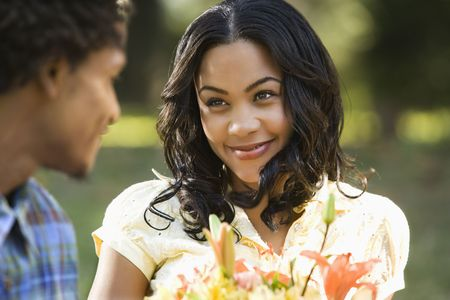 Woman holding flower bouquet smiling at man. photo