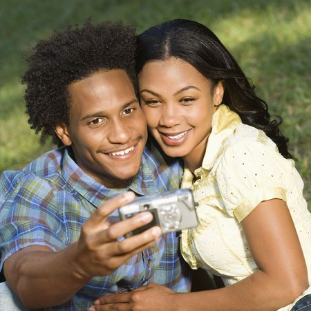 Happy smiling couple taking pictures together in park with digital camera. Stock Photo - 2115370