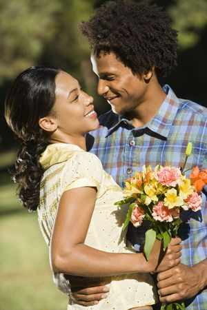 Woman holding flower bouquet and embracing man as they smile at eachother. photo