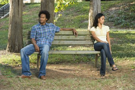 Man and woman sitting on opposite sides of park bench looking away from eachother.