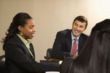 Business people sitting at conference table talking and smiling. photo