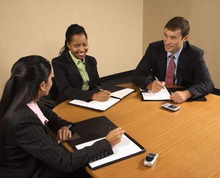 Businesspeople sitting at conference table talking and smiling. photo