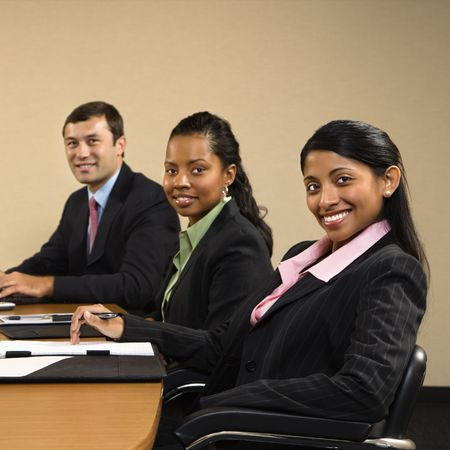 Businesspeople sitting at conference table smiling. photo
