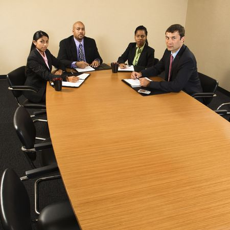 Businesspeople sitting at conference table. photo