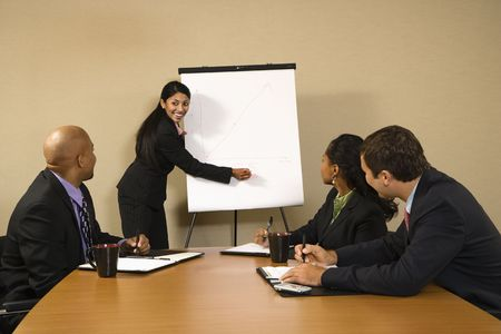 charting: Businesspeople sitting at conference table smiling while businesswoman gives presentation.