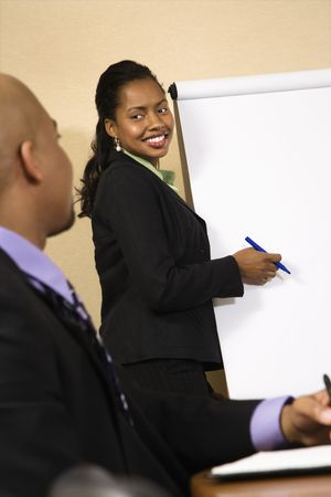 office presentation: Businesspeople sitting at conference table  while businesswoman gives presentation.