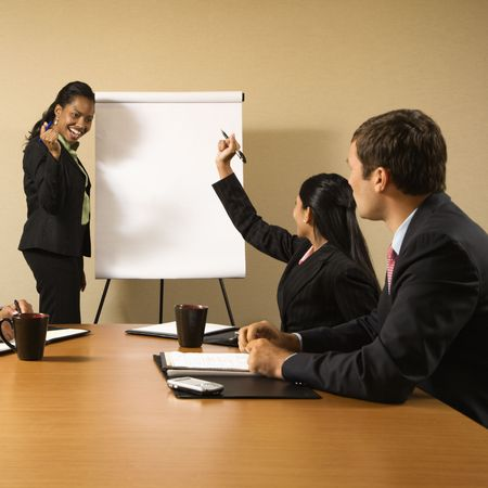 presenting: Businesspeople sitting at conference table  while businesswoman gives presentation.